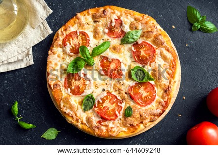 Pizza Margherita on black stone background, top view. Pizza Margarita with Tomatoes, Basil and Mozzarella Cheese close up. #644609248