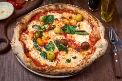 Pizza Napoli, Classic italian pizza with tomato sauce, mozzarella cheese, anchovy and basil on dark a wooden table.