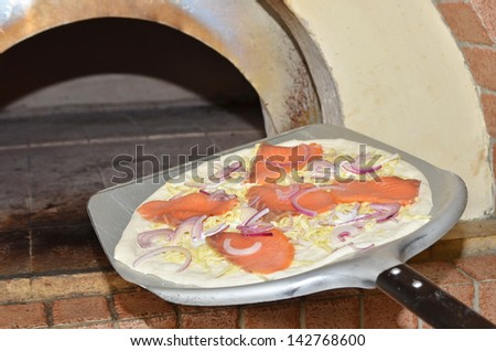 Pizza on  spatula ready to go into oven