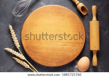 Pizza or bread cutting board with bakery ingredients for homemade baking on table. Food recipe concept at stone background texture with copy space. Flat lay top view