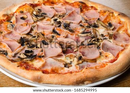 Pizza prosciutto e funghi, traditional italian oven baked dough with toppings: tomato sauce, mozzarella, ham, mushrooms. Simple brown wooden table restaurant setting, closeup and macro shot Foto d'archivio ©