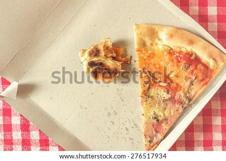 Pizza Slice and Fast Food Leftovers in Cardboard Box on Kitchen Table, Retro Style Toned Image, Selective Focus with Shallow Depth of Field