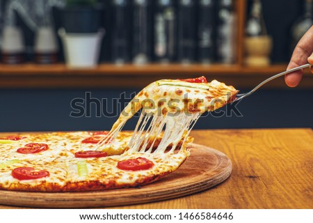 Pizza slice, growing cheddar cheese, restaurant table