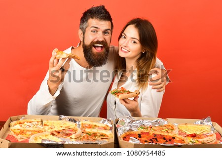 Pizza time. Fast food. Loving couple enjoying pizza. Man and woman eating pizza. Romantic couple - bearded man hugs his girlfriend, eating pizza. Dating. Happy family time. Isolated on red background.