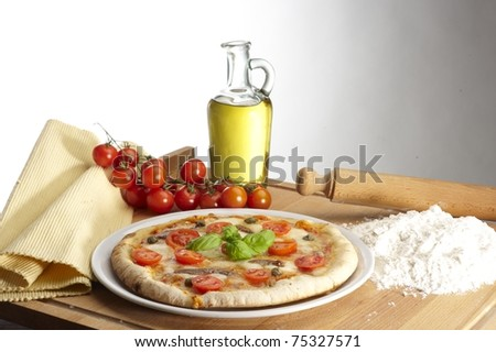 pizza with a bottle of olive oil and tomatoes on a white background