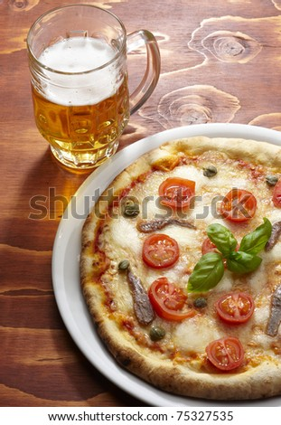 pizza with a glass of beer on the wooden table