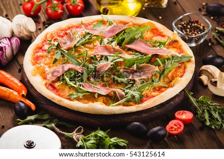 Pizza with bacon and arugula on wooden table (close)