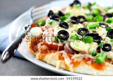 Pizza with cheese and vegetables on wooden rustic table