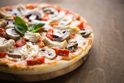 Pizza with chicken, tomato and mushrooms close up