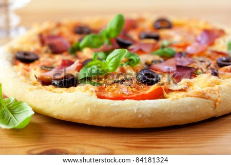 Pizza with ham and tomatoes on wooden background
