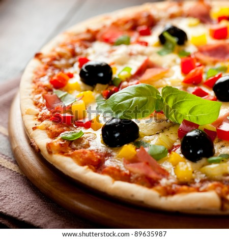Pizza with ham, yellow and red pepper black olives and fresh basil. Italian pizza. Home made food. Symbolic image. Concept for a tasty and healthy meal. Selective focus. Close up.