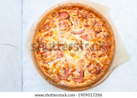 Pizza with mozzarella cheese, ham, tomatoes and sauce on plain grey background Photo stock ©