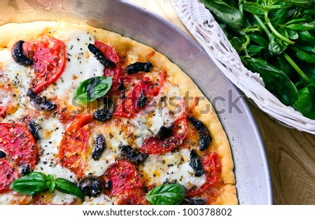 Pizza with mozzarella, tomatoes, mushrooms and basil