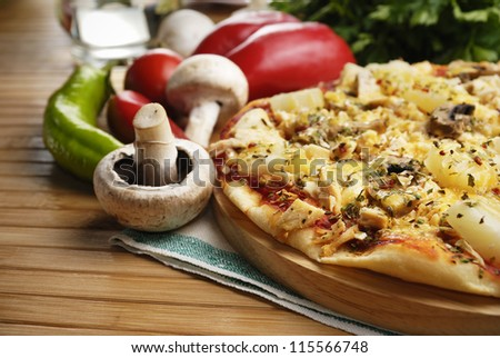 Pizza with mushrooms and pineapples on the kitchen table along with vegetables