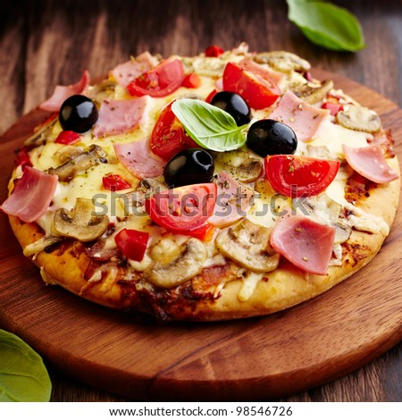 Pizza with mushrooms, ham and cherry tomatoes - stock photo