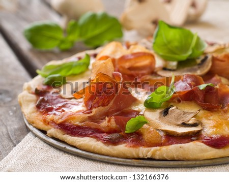 Pizza with prosciutto, mushroom and basil, selective focus