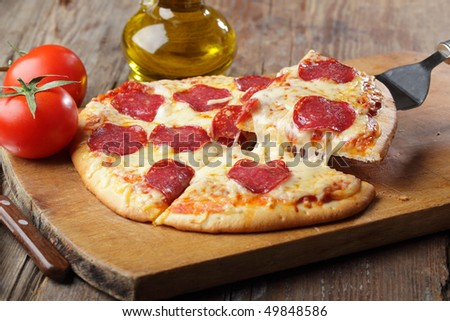 Pizza with salami and cheese on a cutting board