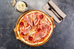 Pizza with salami and prosciutto on wooden board on dark background