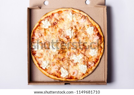 Pizza with seafood shrimps and salmon in packing box on gray background. #1149681710
