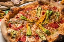 pizza with sliced zucchini, courgette flowers, tomatoes and ham, appetizing round pizza with crispy edge top view, close up