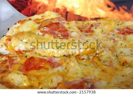 Pizza with smoked streaky bacon, pineapple, ham and pepperoni by clay oven, macro with copy space