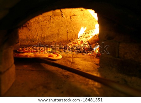 Pizzas baking in an open firewood oven