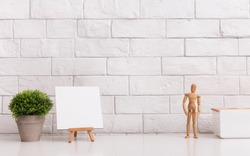 Place for creation. Modern office table with wooden mannequin and easel over white bricks wall