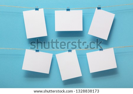 place for photo cards, empty blanks attached to a linen rope in two rows with clips on a colored background, a concept template for text, images, idea for home decor