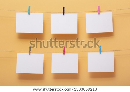 place for photo cards of pleasant  moments, empty blanks attached to a linen rope in two rows withstationery clips on a colored background,template for reminder notes