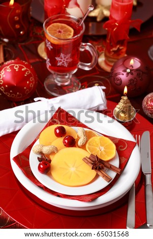 Place setting for Christmas with fresh fruits and hot wine punch