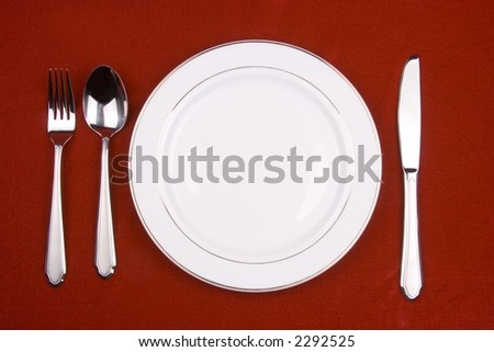 Place setting of a dinning set in red background.