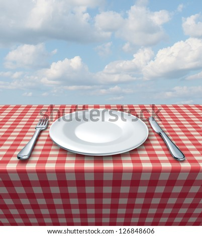 Place setting with a fork knife and white empty plate on a checkered red and white tablecloth on a summer blue sky as a food service and classic restaurant symbol and picnic dining.