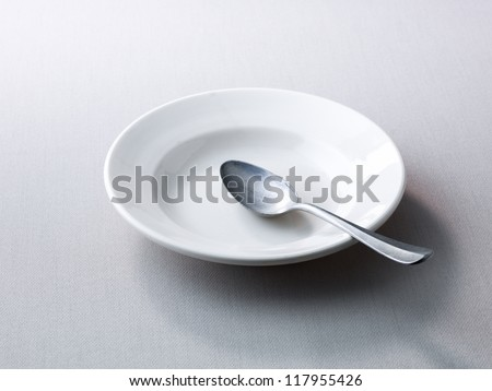 Place setting with empty plate and spoon