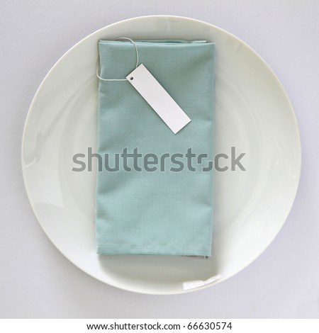 Place setting with plate, linen napkin and tag for name isolated on white background