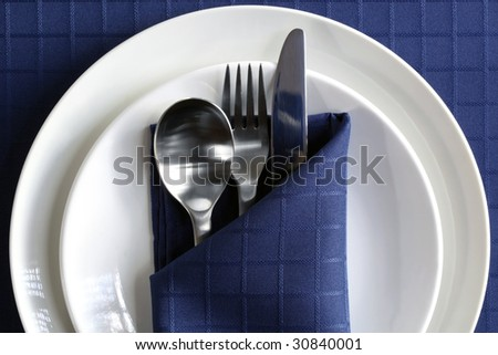 Place setting with plates, silverware, and navy blue napery.