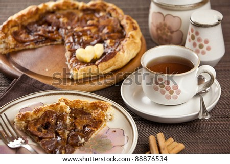 Place setting with romantic heart shaped sliced apple pie and cup of tea or coffee