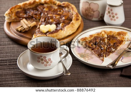 Place setting with romantic heart shaped tart, slice of apple pie and cup of tea or coffee. With cinnamon sticks