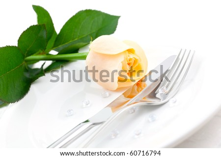 place setting with rose and cutlery - stock photo