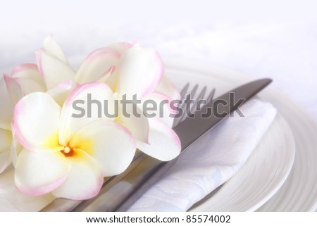 Place setting with white linen and plumeria (frangipani) flowers.