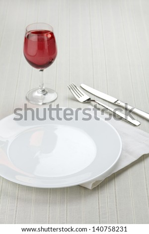 Place setting with white plates and red wine