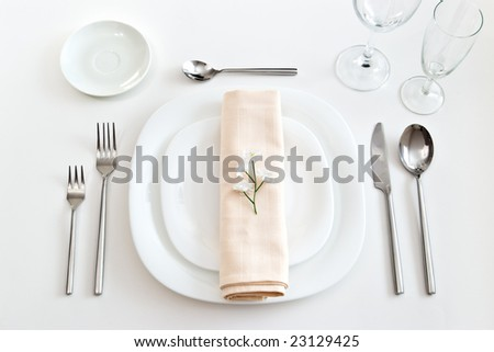 place setting with white plates forks glasses beige napkin and little flower