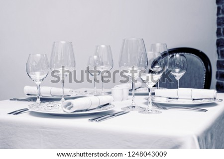 Place setting with wine glasses in an expensive restaurant, toned image