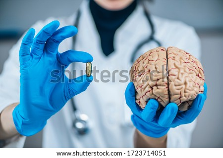 Placebo Effect Concept. Female doctor holding model of brain and placebo supplement pill, explaining the placebo effect healing phenomenon ストックフォト ©