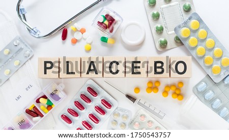 PLACEBO Word Written In Wooden Cubes on a white table with medicines and a stethoscope ストックフォト ©