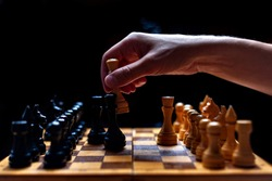 placed chess pieces on a dark background, the concept of confrontation, fair and unfair play, political games, rivalry in business