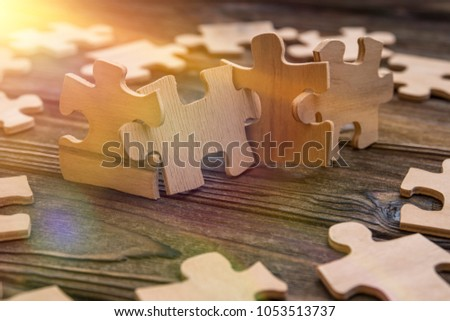 Placement of puzzle pieces in a row on a textured rustic wooden table. Concept business, teamwork and cooperation, strategy, cooperation #1053513737