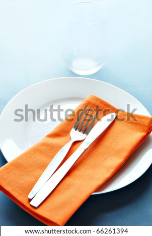 placesetting with plate, fork, knife and napkin and glass