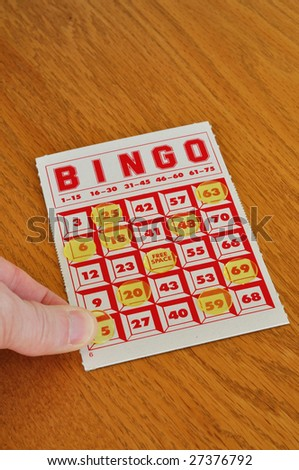 Placing marker on a winning bingo card, vertical with copy space