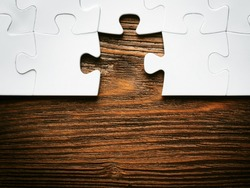 Placing missing a piece of puzzle. business concept. wooden background