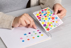 Placing tiny stickers in a notebook
